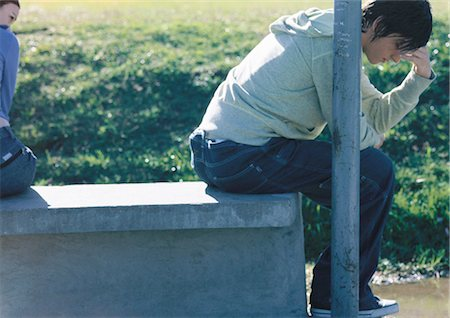 sad lovers break up - Teenage boy sitting on bench, his back turned to his friend holding his head, partial view Stock Photo - Premium Royalty-Free, Code: 632-01150074