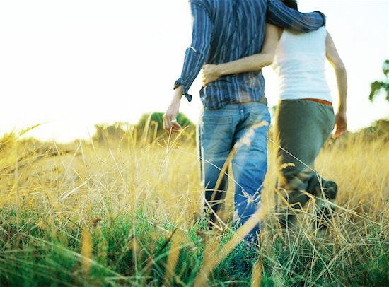 Couple walking through field, rear view, low section Stock Photo - Premium Royalty-Free, Image code: 632-01150328