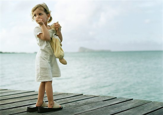Little girl standing on dock, sucking thumb and looking over shoulder Stock Photo - Premium Royalty-Free, Image code: 632-01150338