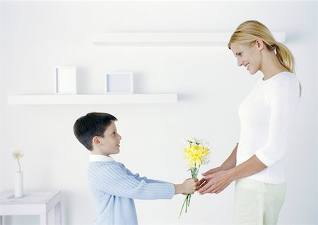 Boy holding out flowers to mother Stock Photo - Premium Royalty-Free, Code: 632-01151570