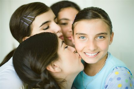 preteen kissing - Four young female friends, three kissing one girl's cheek Stock Photo - Premium Royalty-Free, Code: 632-01380411