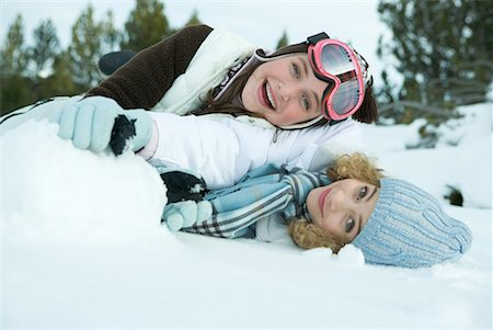 Two young friends reclining in snow, smiling at camera, one on top of the other Stock Photo - Premium Royalty-Free, Code: 632-01612961