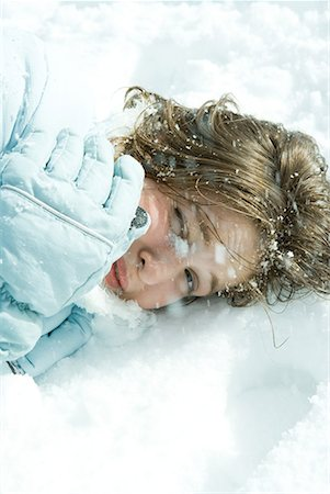 Teenage girl reclining in snow, looking at camera, close-up Stock Photo - Premium Royalty-Free, Code: 632-01612997