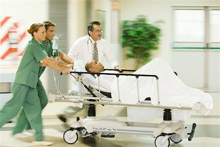 patient walking hospital halls - Emergency room staff pushing man on stretcher, blurred motion Stock Photo - Premium Royalty-Free, Code: 632-01613006