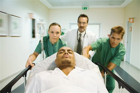 patient walking hospital halls - Emergency room staff pushing man on stretcher Stock Photo - Premium Royalty-Free, Code: 632-01613009
