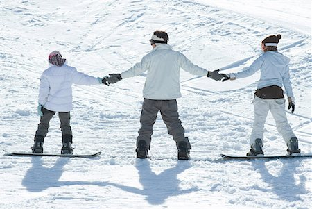 Three young snowboarders standing together, holding hands, rear view Stock Photo - Premium Royalty-Free, Code: 632-01613224