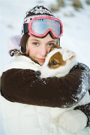 Teenage girl embracing dog, dressed in winter clothing, smiling at camera, portrait Stock Photo - Premium Royalty-Free, Code: 632-01638416
