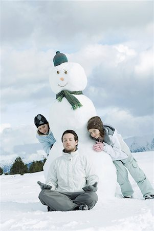 Young man meditating in front of snowman, two girls creeping up behind him Stock Photo - Premium Royalty-Free, Code: 632-01638778