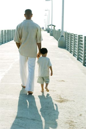 forward - Father and son walking together, holding hands, rear view Stock Photo - Premium Royalty-Free, Code: 632-01827727