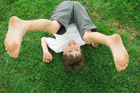 Boy lying on the ground with legs in the air, smiling at camera, high angle view Stock Photo - Premium Royalty-Free, Code: 632-02008067