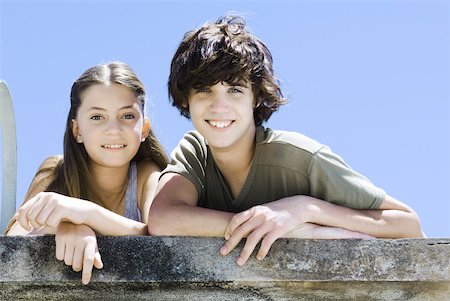 Brother and sister side by side, leaning on concrete wall, smiling at camera, portrait Stock Photo - Premium Royalty-Free, Code: 632-02128261