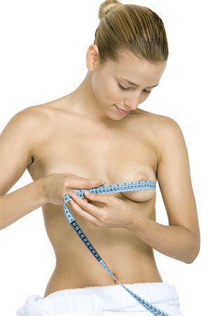 Woman wrapping measuring tape around chest, looking down at breasts, smiling Stock Photo - Premium Royalty-Free, Code: 632-02128353