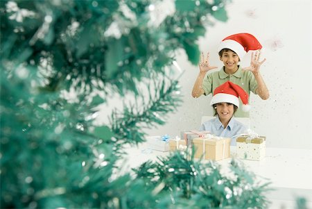 Boys with Christmas gifts, wearing Santa hats, smiling at camera Stock Photo - Premium Royalty-Free, Code: 632-02128396