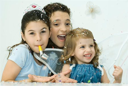 family image and confetti - Woman celebrating with daughters on her lap, confetti everywhere Stock Photo - Premium Royalty-Free, Code: 632-02128422