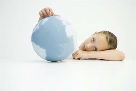 Girl holding globe, head resting on arms, looking at camera Stock Photo - Premium Royalty-Free, Code: 632-02282560