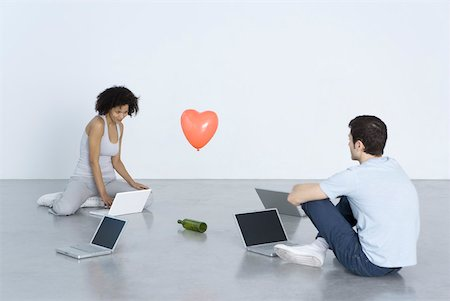 """female silhouettes heart - Man and woman sitting with laptop computers, playing """"spin the bottle"""" Stock Photo - Premium Royalty-Free, Code: 632-02283055"""