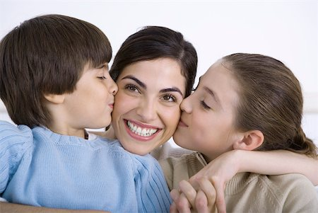 Mother being kissed on each cheek by young daughter and son, smiling Stock Photo - Premium Royalty-Free, Code: 632-02345165