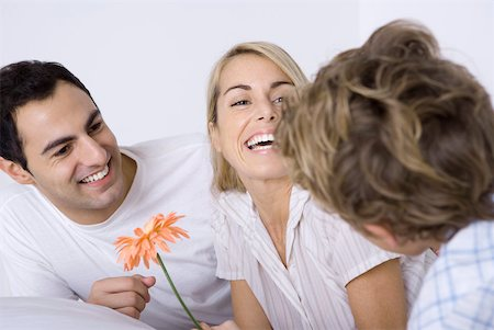 Woman laughing with husband and son, holding flower Stock Photo - Premium Royalty-Free, Code: 632-02345214