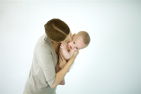Mother kissing infant on the cheek, baby looking down Stock Photo - Premium Royalty-Free, Code: 632-02416236