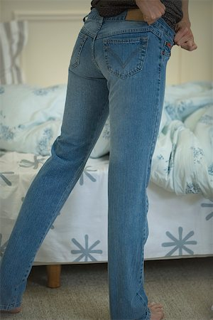 Woman putting on snug-fitting jeans, cropped view Stock Photo - Premium Royalty-Free, Code: 632-02645061