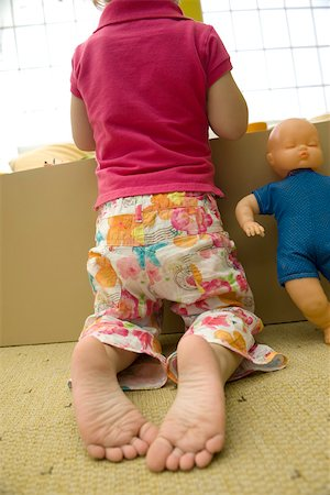 Little girl kneeling before box of toys, rear view Stock Photo - Premium Royalty-Free, Code: 632-02645119
