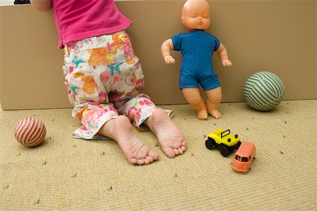 Little girl kneeling on floor with toys, rear view, cropped Stock Photo - Premium Royalty-Free, Code: 632-02645139