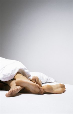 Feet of couple lying together emerging from under blanket, cropped view Stock Photo - Premium Royalty-Free, Code: 632-02689996