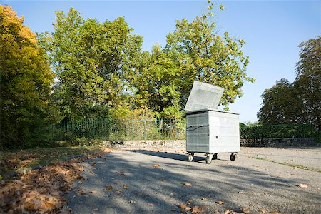 Small dumpster in parking lot at edge of wooded area Stock Photo - Premium Royalty-Free, Code: 632-02690384