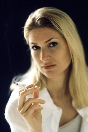 Woman holding cigarette, portrait Stock Photo - Premium Royalty-Free, Code: 632-02744693