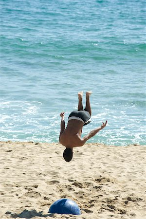 Teen boy doing back flip on beach Stock Photo - Premium Royalty-Free, Code: 632-02745241