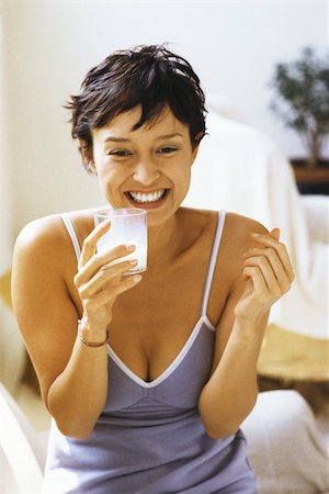 Woman smiling, holding glass of milk Stock Photo - Premium Royalty-Free, Code: 632-03027012