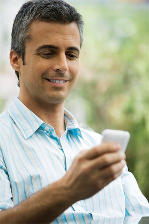 Man text messaging with cell phone Stock Photo - Premium Royalty-Free, Code: 632-03027454