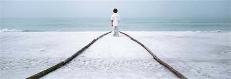 Boy standing at end of footpath on beach, looking at sea Foto de stock - Sin royalties Premium, Código: 632-03083012