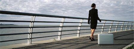 forward - Briefcase set on ground near waterfront railing, businesswoman walking away Stock Photo - Premium Royalty-Free, Code: 632-03083042