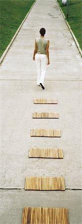 forward - Woman walking along footpath, rear view Stock Photo - Premium Royalty-Free, Code: 632-03083062