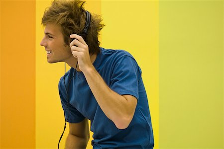 Young man listening to headphones Stock Photo - Premium Royalty-Free, Code: 632-03083630