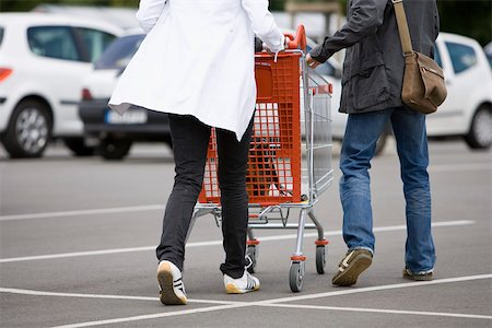 person walking on parking lot - Shoppers pushing shopping cart in parking lot Stock Photo - Premium Royalty-Free, Code: 632-03193717
