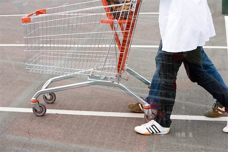 empty shopping cart - Empty shopping cart being pushed across parking lot Stock Photo - Premium Royalty-Free, Code: 632-03193742