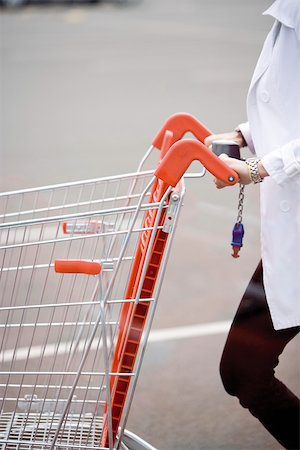 empty shopping cart - Shopping cart being pushed across parking lot Stock Photo - Premium Royalty-Free, Code: 632-03193751