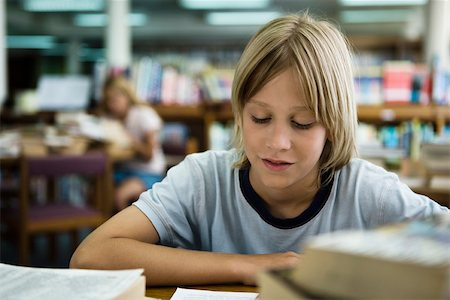 Boy reading in library Stock Photo - Premium Royalty-Free, Code: 632-03403388