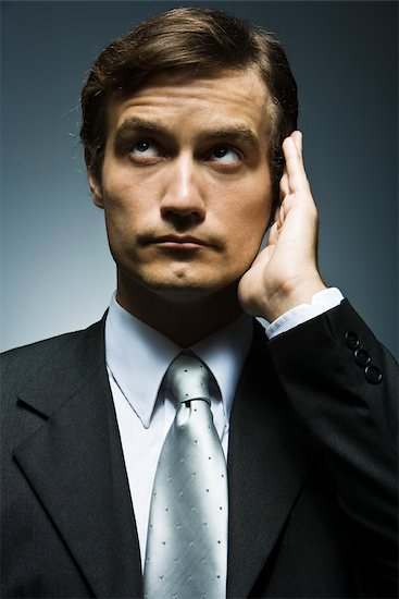 Businessman with hand cupped around ear listening attentively Stock Photo - Premium Royalty-Free, Image code: 632-03403433