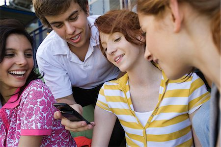 Teenage friends together, boy showing girl cell phone, others looking with amusement Stock Photo - Premium Royalty-Free, Code: 632-03424168