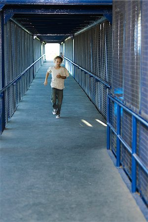 running away scared - Preteen boy running down corridor, front view Stock Photo - Premium Royalty-Free, Code: 632-03424195