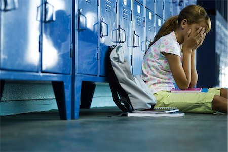 preteen girl - Female junior high student sitting on hall floor near lockers, upset and covering face with hands Stock Photo - Premium Royalty-Free, Code: 632-03424192