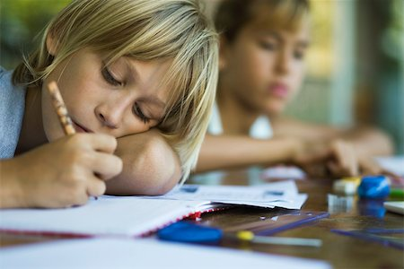 Junior high student resting head on arm while writing assignment Stock Photo - Premium Royalty-Free, Code: 632-03424202