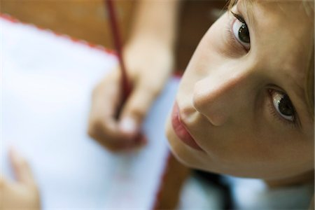 Boy writing in notebook, pausing work to look up at camera Stock Photo - Premium Royalty-Free, Code: 632-03424215