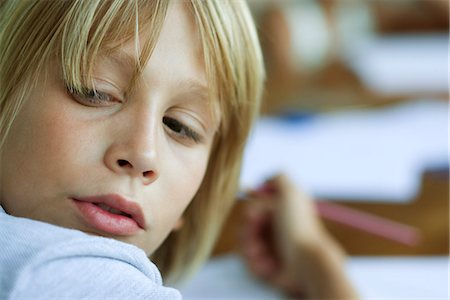 Boy looking over shoulder, distracted from work Stock Photo - Premium Royalty-Free, Code: 632-03424217