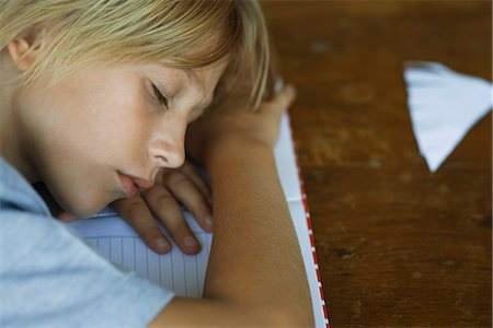 Preteen boy sleeping, resting head on arms laid across notebook Stock Photo - Premium Royalty-Free, Code: 632-03424213