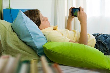 preteen boys playing - Preteen boy playing handheld video game Stock Photo - Premium Royalty-Free, Code: 632-03424261