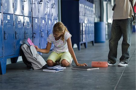 Junior high student picking up dropped school supplies, boy standing by watching Stock Photo - Premium Royalty-Free, Code: 632-03424528